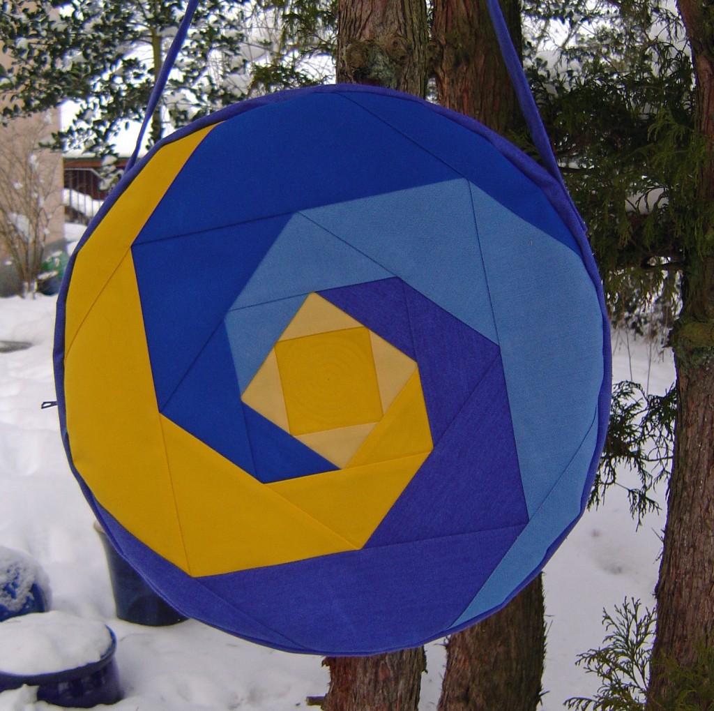 Trommeltasche mit Spiralen in blau und gelb. Mitte gelb