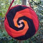 Trommeltasche mit Patchwork-Spiralen in rot, pink, orange und schwarz, mit Quilting