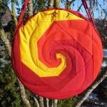 Trommeltasche mit Patchwork-Spiralen in gelb und diversen Rot, gequiltet