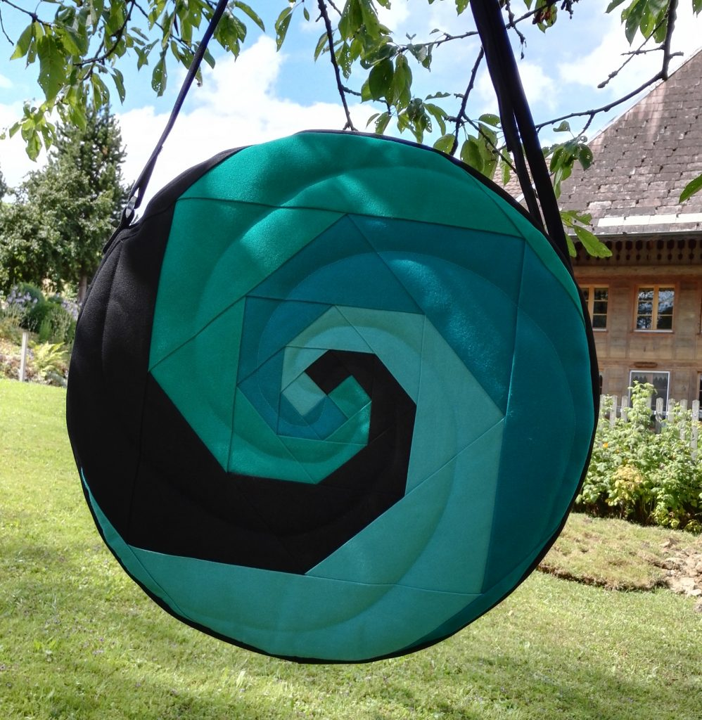 Trommeltasche mit Spiralen in türkis und schwarz.